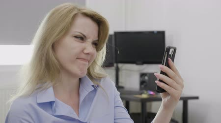 disapprove : Displeased young employee with formal wear at work sliding media content on her smartphone display waving head no in full disagreement