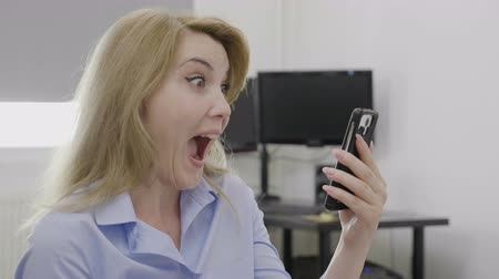 восхищенный : Surprised joyful female entrepreneur receiving good news about her business results on her mobile phone feeling satisfied and excited success and achievement concept Стоковые видеозаписи