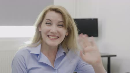 cortes : Cheerful corporate young woman waving hand saying hello in the office