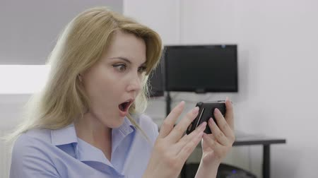 údiv : Shocked young businesswoman receiving surprising breaking news on her smartphone at work