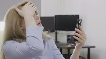 betrokken : Portrait of upset businesswoman sliding content on her smartphone feeling annoyed slapping her forehead in disbelief gesture facepalm concept