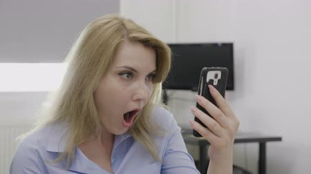 удивительный : Jaw dropped office woman surfing on social media network using smartphone staring in shock at screen watching something disturbing