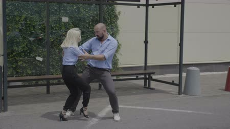 развлекательный : Professional latino dancers showing their skills in public near a bus station
