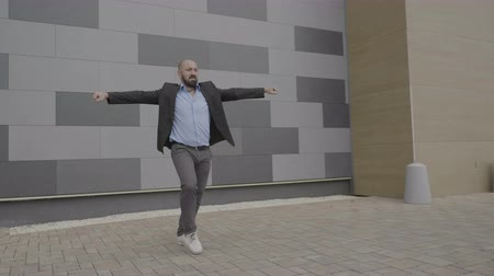 resmi bir takım : Enthusiastic employee man feeling empowered dancing in public near his workplace showing salsa moves artistic Stok Video