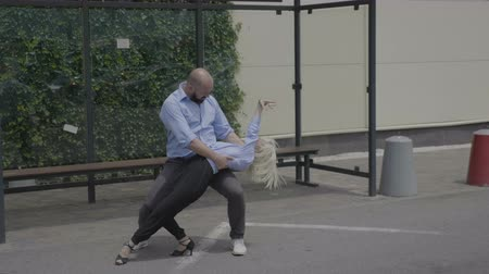 skillful : Professional latino dancers showing their skills in public near a bus station