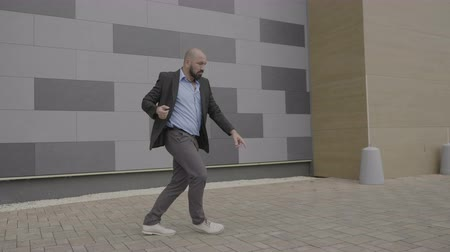 humor : Confident businessman dancing freestye dance on his way to work on the street