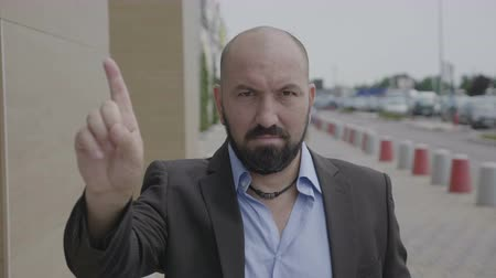 odmítnutí : Business man waving index finger doing no gesture expressing denial outdoor