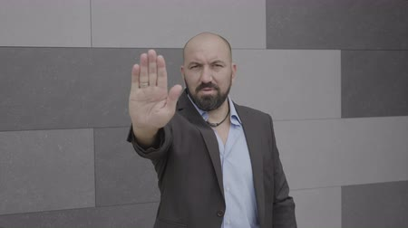 odmítnutí : Serious business man showing stop hand gesture expressing denial on city street
