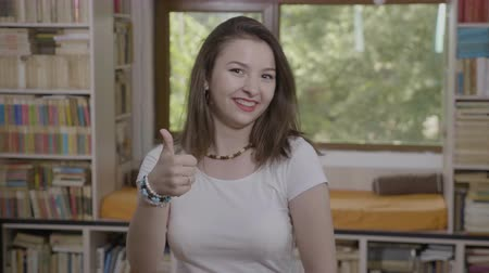 approving : Portrait of cheerful young woman smiling and showing thumbs up