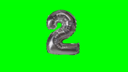воздушный шар : Number 2 two years birthday anniversary silver balloon floating on green screen Стоковые видеозаписи