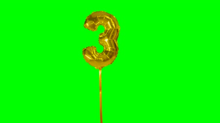 golden color : Number 3 three years birthday anniversary golden balloon floating on green screen