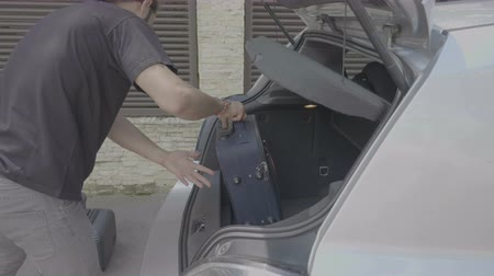rekesz : Cheerful young man taking off luggage from the trunk of parked car arriving at destination car travel concept Stock mozgókép