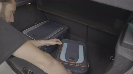 rekesz : Young entrepreneur male orderly organize his suitcases inside the trunk car for a business trip