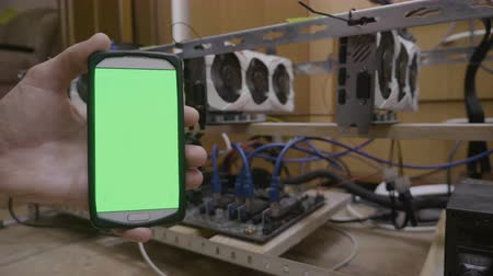 gpu : Smartphone with green screen display next to cryptocurrency mining rig held by developer trader man touching screen typing code Stock Footage