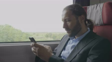 ileri : Young entrepreneur man commuter on train sitting next the window using smartphone on his way to office Stok Video