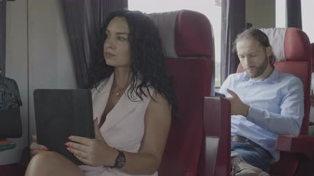 旅行の目的地 : Technology addiction of millennial office dressed man and woman commuters on train using tablet and smartphone during their journey 動画素材