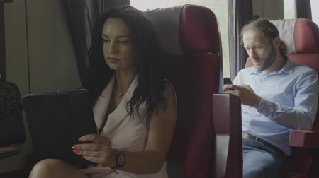 sáně : Business man and woman commuting to work using tablet and smartphone surfing on internet technology and train travel with train concept