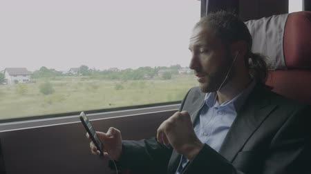 tárcsázás : Confident young entrepreneur man traveling by train having a business video call on digital smartphone application explaining and gesturing during his trip to office work