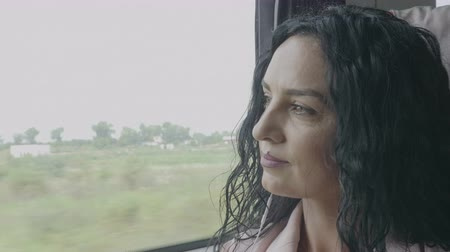 contemplative : Daydreaming young woman enjoying voyage looking outside of the train window relaxing and listening to music on smartphone wearing earphones