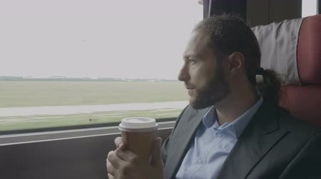 voyager : Contemplative businessman commuter on train drinking coffee and admiring the landscape outside the window during the travel to work