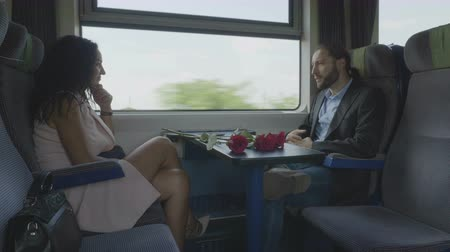 voyager : Voyage of elegant young couple traveling together on railway train wagon talking each other and flirting with roses between them Stock Footage