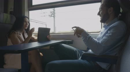 voyager : Young tourist couple traveling on vacation by train having fun talking and using their digital smart devices during the journey Stock Footage