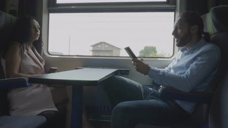 rekesz : Corporate employees man and woman or coworkers enjoying conversation while they using their gadget on train compartment commuting to office Stock mozgókép