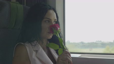 センチメンタル : Romantic young woman smelling roses and looking thoughtful outside the window departing on train