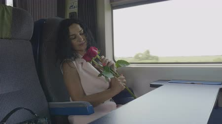 センチメンタル : Young woman in love on train admiring roses received from her valentine love and travel concept