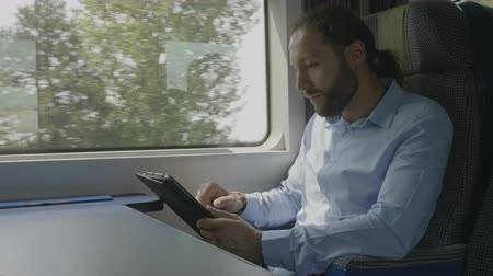 dojíždění : Focused young entrepreneur swiping and scrolling on tablet touchscreen surfing on internet next to window in moving train