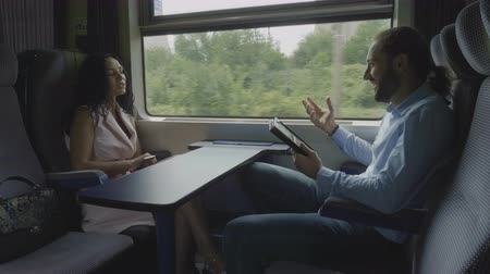 departing : Young business man commuting from work to home using a tablet pc talking and flirting with elegant attractive young woman during travel Stock Footage
