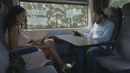 voyager : Woman and man traveling on train being non communicative using their smartphones to passing time addicted to online social media Stock Footage