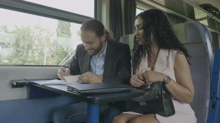 departing : Young bearded business partner filling information and signing the contract agreement discussing with businesswoman during the professional trip Stock Footage