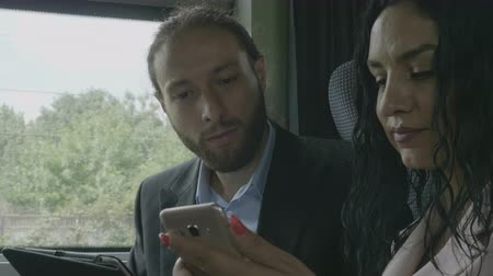 departing : Closeup of young business partners couple sitting in a moving train talking and analyzing business information on smartphone Stock Footage