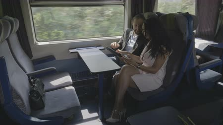 debata : Young corporate couple man and woman discussing about business project using their device tablet pc and smartphone while they traveling by train