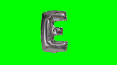 word balloon : Big Letter E from alphabet helium silver balloon floating on green screen Stock Footage