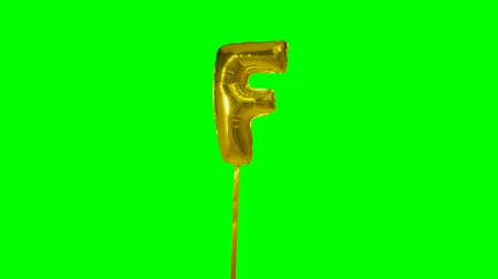 letter f : Letter F from alphabet helium gold balloon floating on green screen Stock Footage
