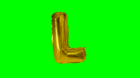 lápide : Big Letter L from alphabet helium gold balloon floating on green screen
