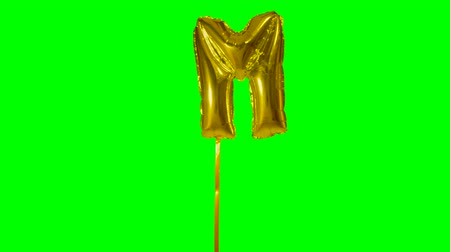 sziám : Letter M from alphabet helium gold balloon floating on green screen