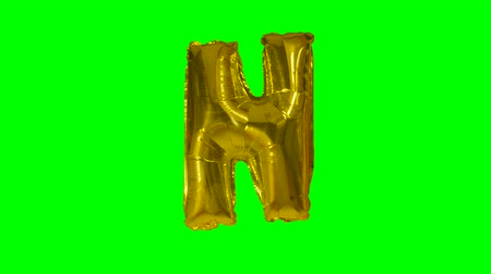 глянцевый : Big Letter N from alphabet helium gold balloon floating on green screen