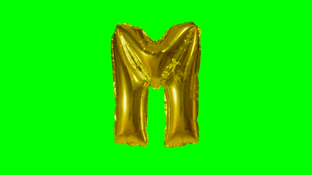 sziám : Big Letter M from alphabet helium gold balloon floating on green screen