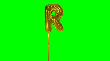 sto : Letter R from alphabet helium gold balloon floating on green screen