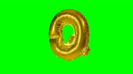 книгопечатание : Big Letter Q from alphabet helium gold balloon floating on green screen Стоковые видеозаписи