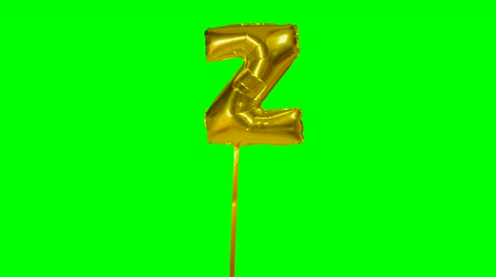 word balloon : Letter Z from alphabet helium gold balloon floating on green screen Stock Footage
