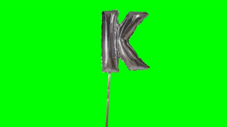 bab : Letter K from alphabet helium silver balloon floating on green screen Stock mozgókép