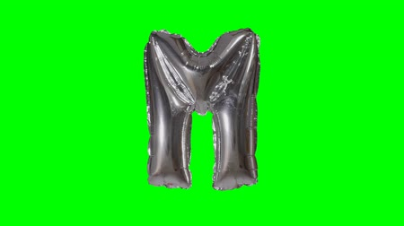 folyo : Big Letter M from alphabet helium silver balloon floating on green screen Stok Video