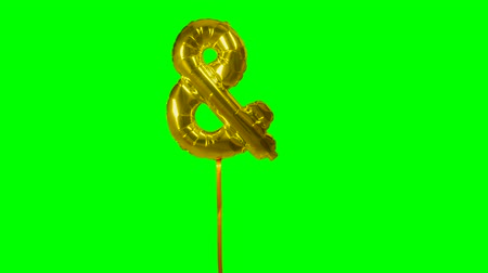 глянцевый : Sign symbol ampersand and from alphabet helium gold balloon floating on green screen Стоковые видеозаписи