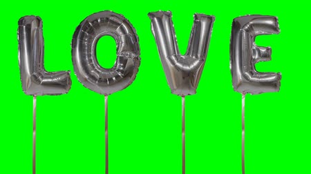 soletrar : Word love from helium silver balloon letters floating on green screen