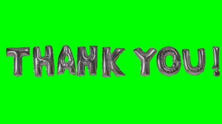 soletrar : Word thank you from helium silver balloon letters floating on green screen