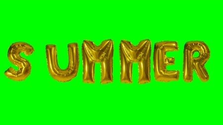 betűtípussal : Word summer from helium gold balloon letters floating on green screen Stock mozgókép